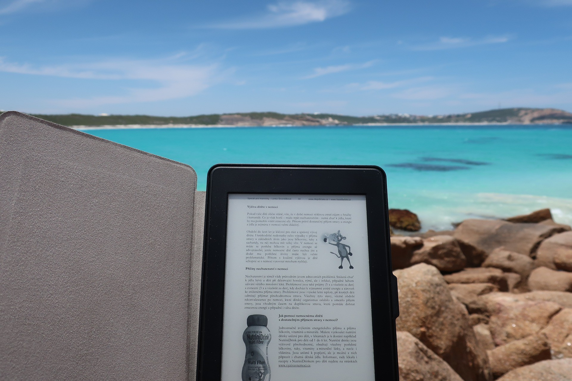 a tablet device with some reading material at a beach