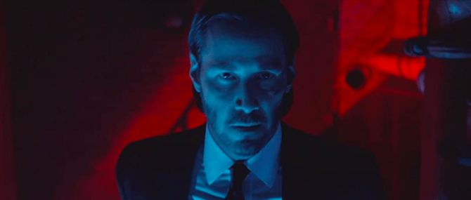 A movie still from John Wick shows John Wick (played by Keanu Reeves) bathed in a blue light. Behind him is a red light pouring out of a window.
