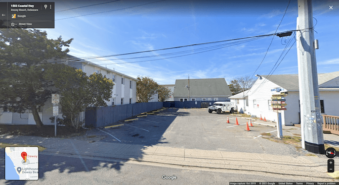 A Google Maps search for the Dewey Beach Town Hall shows this view of an empty parking lot and a small white building beside it.