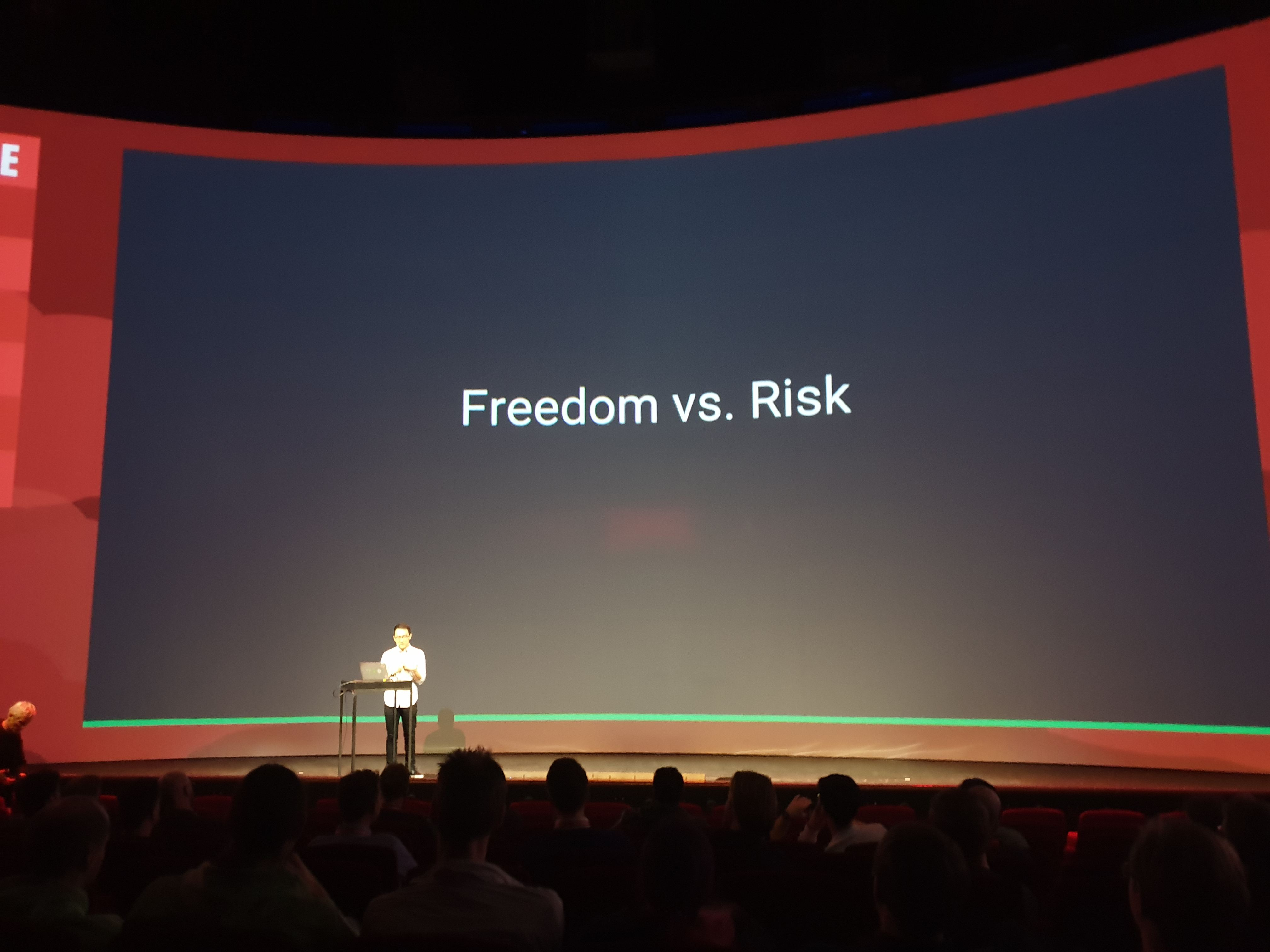 Evan You stands on stage in front of a slide that reads Freedom vs. Risk