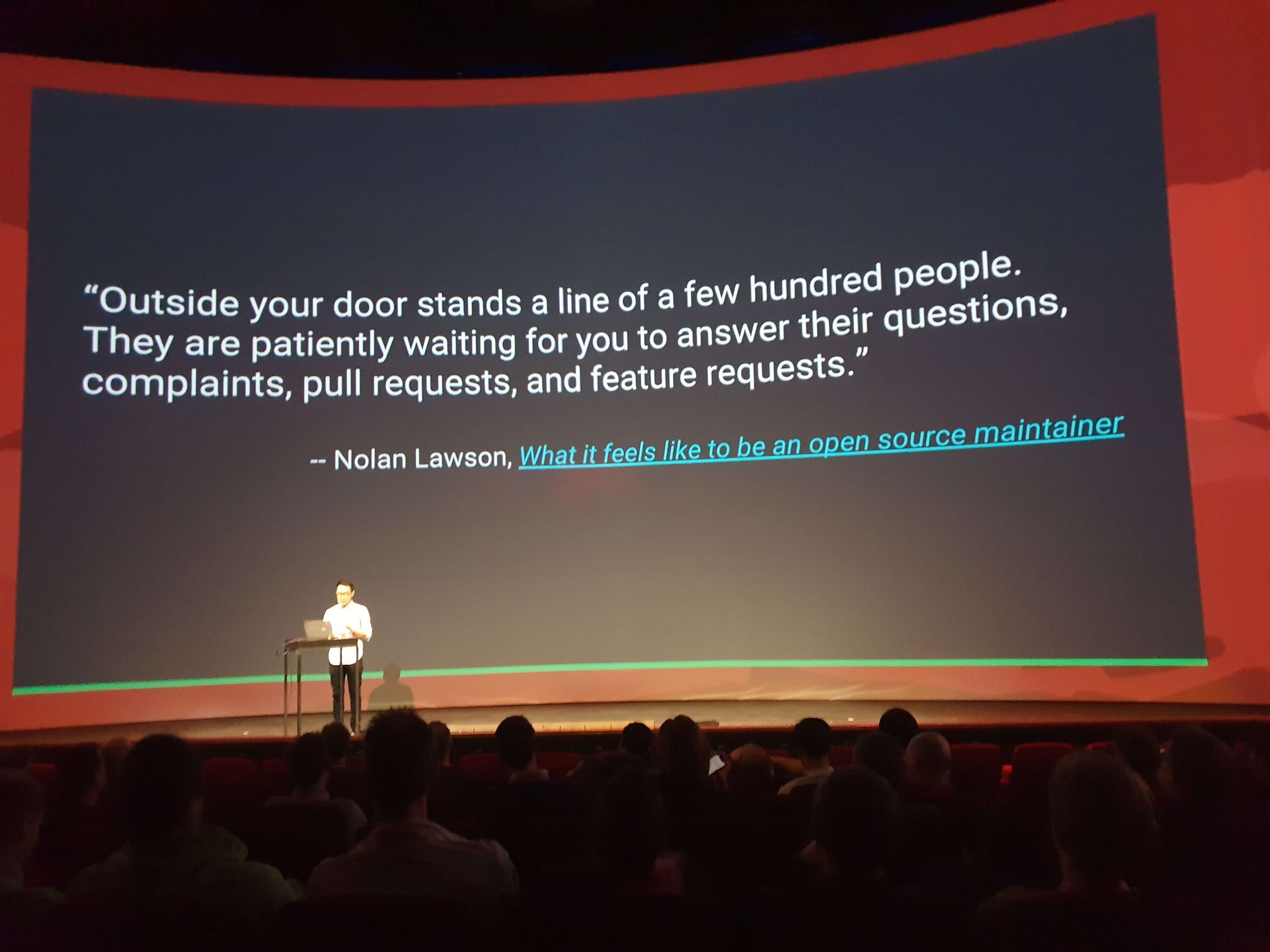 "Evan You on stage in front of a slide with a quote by Nolan Lawson. It reads, ""Outside your door stands a line of a few hundred people. They are patiently waiting for you to answer their questions, complaints, pull requests, and feature requests."""